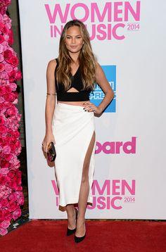 Chrissy Teigen combina su falda midi en color blanco con un 'crop top' negro a juego con sus accesorios, salones y 'clutch'.
