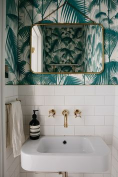 The downstairs powder room is papered in Cole & Son Palm Jungle Wallpaper. Fixtures and fittings include a hanging Brass Frame Mirror, Perrin & Rowe Faucet, and Futagami Brass Towel Bars.