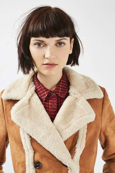 Invest in a chic outerwear piece this winter. Crafted from faux shearling, this coat is guaranteed to keep you warm throughout the colder months. Featuring button up fastening and practical pockets, this stylish piece is perfect for throwing over your knitwear. #Topshop