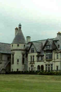 "Carey Mansion, originally called Seaview Terrace, is a sprawling French Renaissance château located in Newport, Rhode Island. It was the last of the great ""Summer Cottages"" constructed, and is the fifth-largest of Newport's mansions.  The television show Dark Shadows used its exterior as the fictional Collinwood Mansion. In a 2011 episode of ""Ghost Hunters"", The Atlantic Paranormal Society claimed to have found ample evidence that the mansion was haunted.Until recently, part of the main house and some of the outbuildings were leased to Salve Regina University.The majority of the house was originally built in DuPont Circle in Washington, DC by liquor baron Edson Bradley in 1907, taking 4 years to complete. The house occupied an entire city block and was  known as Aladdin's Palace, due to its sheer size and grandiose nature.  The Bradleys then decided to move to a Newport, Rhode Island in February of 1923. They had the house dismantled and shipped to the new location over the next two years, accomplishing what is believed to be one of the largest homes to be relocated by road and rail. This remarkable feat was featured on 'Ripley's Believe it or Not"".  Howard Greenly, the architect of Seaview Terrace, won several awards for his work on the French Gothic chateau in 1928, including the 'Second Mention for General Work' by the Architectural League of New York and the President's medal from the American League of Architects.  Greenly incorporated the pre-existing Elizabethan-Revival mansion into the house, which had been owned by James Kernochan and known as Sea View.  The earlier Sea View  is still visible, encased in the East Wing of the house and was renamed Seaview Terrace.   The roofline of the turrets and conical domes were derived from Chambord, a famous French Renaissance chateau in the Loire Valley, and impart a picturesque unity to the whole.   A housewarming was held in the summer of 1925, as Greenly continued to move rooms fully intact from France, as well as contents of the DuPont Circle house for installation at the seaside locale. At the end of that year, the 63 room manor was completed at a cost of two million dollars. It featured a chapel, whispering gallery, an Esty  organ and Dutch sixteenth century stained glass, ornamented with Renaissance armoral design. Included in the stained glass collection is the 'Flagellation' circa 1545, which is documented in the national archives. Original furnishings included bearskin rugs, hunting trophies, Renaissance cassones, wrought iron torcheres, Chippendale chairs, arms and armor and exotic hanging lamps. In January of 1930, the Bradley's daughter, Julie Fay Bradley Shipman, was deeded the property by her father, the same year her husband, Rt. Rev. Herbert Shipman, the protestant Episcopal bishop of New York and a World War I army chaplain passed away.  On July 24,1942 the City of Newport took title due to back taxes and during World War II, the house served as army officer's quarters.  In 1949 Edward J. Dunn bought the property for $8000, transferring title to Mrs. George Waldo Emerson Sr., who in turn leased it to Lloyd H. Hatch, making it headquarters for The Hatch School during the fall and spring semesters from 1951-1961. During the summers, Mrs. Emerson Sr. operated Burnham-by-the-Sea, a private all-girls boarding school which ran in association with the Mary Burnham School for Girls in Northampton, MA. After the Hatch school vacated the property  it was then rented to The Newport School for Girls  who enjoyed their summers there until the early 1970's.   During 1966-1971, Seaview Terrace's  turreted profile became the icon for the cult classic TV show 'Dark Shadows', which continues to draw thousands of loyal fans annually.   With a great passion and appreciation for the arts, architecture and history, Martin and Millicent Carey of New York purchased the mansion in 1974 and soon commenced renovations to the exterior and interior of the estate. This included commissioning the talented Donald and Harle Tinney, the owners of Belcourt Castle and highly celebrated stained-glass and leaded window artisans, to restore the windows in the Solarium, Chapel and Great Hall.    The 1980's in Newport belonged to the America's Cup. Led by Ca. Dennis Connor, the American syndicate resided at Seaview Terrace  during their reign. The remainder of the year the house was leased to Salve Regina University as a musical conservatory, educational facility and student residence until 2009.  The Carey family now continues their vision of restoring this architectural gem to the grandeur it deserves."
