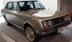"""Toyota Mark 2 1968 - '""""our"""" first car - was forest green with red upholstery.  After a series of adventures, it ended up with a blue door, a red hood, and a beige driver's seat."""