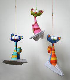 """Ellos vuelan sobre un avión de papel. Confeccionados en papel maché. Medidas: 30 x 8 x 20 cm.  Los puedes encontrar en """"ARCOIRIS"""", calle Avinyo nº 39, Barcelona, España."""