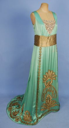 TRAINED SILK and GOLD METALLIC EMPIRE GOWN, c. 1908. Sleeveless mint green satin having beaded net bodice insert and gold lame waistband, trained skirt decorated with heavy metallic gold cord, back closure.