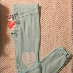 Wildfox Blue Lover Jogger Pants Size Small  NWT Wildfox Couture Light Blue Lover Jogger Pants with white Hearts on the knees. Size Small. Drawstring waist and banded hem. Normal Wildfox pilling. Material does not feel the same as the BBJ's. 95% Cotton, 25% Polyester. Please ask any questions you may have before purchasing. ✨No Trades/PP✨ Wildfox Pants Track Pants & Joggers