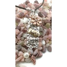 This handmade charm necklace with a daisy on top in copper tone, a long silver tone piece with 'Live', 'Love' and 'Laugh' stamped on the front and smaller charms in antique copper and pearl dangling b