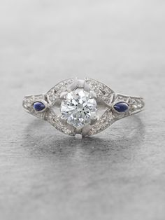 This original Antique Heirloom ring from the Art Deco period (1920's) is handcrafted with incredible attention to detail, featuring a gorgeous round Diamond surrounded by an open arched setting of dia
