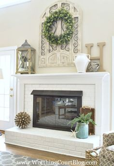 First up is the large metal and wood piece above my fireplace.  It came from Kirklands, but isn't currently available in the lighter finish.  You can repaint it though, which is what I did with mine.  I get asked about the wreath a lot too.  It's a 24″ grapevine wreath that I simply wired three greenery garlands to
