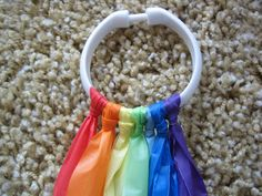 From Teaching The Little People: lRainbow streamers made with shower curtain rings and strips cut from dollar store plastic tablecloths.