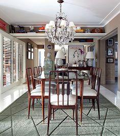Beges, cinzas e brancos pontuam cortinas, paredes, tapetes da casa de André Almada. Móveis de jacarandá dos anos 1950, como essa mesa e cadeiras, lembram a casa de Birigui – cidade onde morou. Projeto do arquiteto Nelson Kabarite