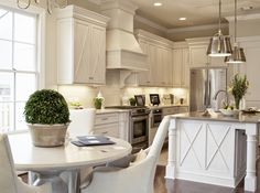 Stunning kitchen with off-white cabinets accented with nickel hardware and white perimeter counters alongside a beige subway tiled backsplash.