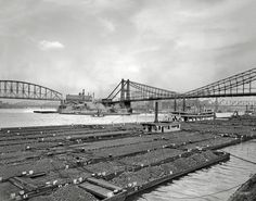 """Circa 1910. """"Coal barges at confluence of Allegheny and Monongahela rivers at Pittsburgh, Pennsylvania."""" 8x10 inch glass negative."""