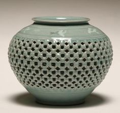 """A Korean celadon ceramic vase; double wall construction with interesting open basket weave design over hand thrown form with a flock of cranes circling the shoulder. 5 1/2""""H. Artist signed on the base."""