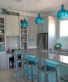 Beachy blue kitchen. Blue kitchen island and blue glass pendant lights.