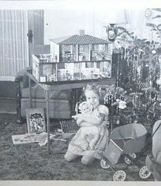 A Christmas Dollhouse, baby doll, buggy. Such a happy little girl! And she must have been a very good little girl for Santa to be so generous. A sweet moment to remember always. Vintage Christmas Photos, Retro Christmas, Vintage Holiday, Christmas Pictures, Silver Christmas, Victorian Christmas, Old Time Christmas, Old Fashioned Christmas, Christmas Past