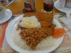 Almoco simples. Bife de peito de frango a milanesa, arroz, feijao ovo frito e salada de tomate.