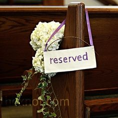Hand-stitched signs reserved the family pews at the church. Clusters of white hydrangeas and ivy adorned each row.