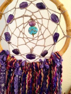 """9 high-grade amethyst beads surrounding a  rare fuxita stone bead and handblown turquoise glass.  Rattan hoop and hemp weave..with soft multi-colored cotton-blend fringe. (30""""L x 6.5"""" W) ************************************************************************Dreamcatchers are known to have mystical effects on people's dreams and sleep patterns. Dream Halos are created to enhance your dreamsand filter out negative energies. According to ancient legend,The ..."""