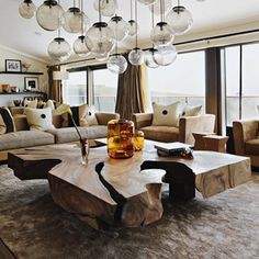 Love the multiple light fixtures at various heights and the ginormous coffee table #coffeetabledesign #moderndesign #livingroom wooden coffee table, modern living room, interior design . Find more inspirations at www.coffeeandsidetables.com