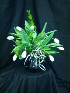 This arrangement was done in a black round glass container with 10 white tulips,  veri pitt, and leather.