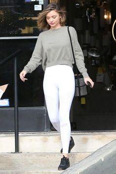 Miranda Kerr wearing Reebok Classic Sneakers, Alaia Suede Grommet Bucket Bag and Alo Yoga Moto Leggings in White