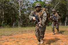 U.S. Marine Corps Lance Cpl. Renea Rivas (front), rifleman, Company E, Battalion Landing Team 2nd Battalion, 4th Marines, (BLT) 31st Marine Expeditionary Unit, moves towards targets while conducting a Helo Raid at Combat Town, Okinawa, Japan, Dec. 8, 2014. Company E is conducting training as part of the MEU Exercise and pre-deployment training. (U.S. Marine Corps Photo by Lance Cpl. Richard Currier/ Released)