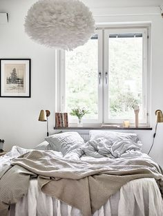 Swedish bedroom with a large pendant light, gold sconces, and white bedding