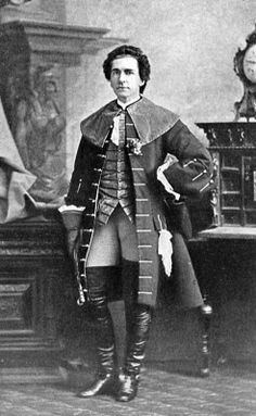 Garrick coat: Garrick Coat- coat that was often made of velvet and trimmed with fur. The Garrick, cut very full to the floor, was an iconic style during the 1880s. The cloak consisted of triple capes over the shoulders, and was cut with ample room so it could be worn over a tail coat or waistcoat