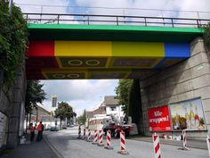 From down the road, the bridge does in fact appear to have been constructed of gigantic LEGO blocks. Passing closer and, eventually, underneath reveals MEGX's clever trick: the toys' familiar features–bright hues, protruding cylinders, inverse voids–are indeed flat, yet rendered in shadow to produce the trompe l'oeil effect. Still, we'll count it.