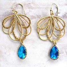 blue crystals are encased in 14k gold plate and dangle from gilded, wispy fans