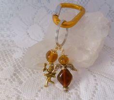 Zauberhafter Schlüsselring mit Klappverschluß in Metallicorange und wunderschönem Behang:  Engelchen und honigfarbene Glasperlen.  Länge ca. 11cm