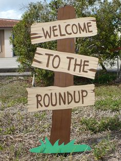 Toy Story Birthday Welcome To The Roundup Standing Sign Western Birthday Decoration, Cowboy Cowgirl Party on Etsy, $22.00. This would be quite easy to duplicate. Cardboard could even be used for the signs.