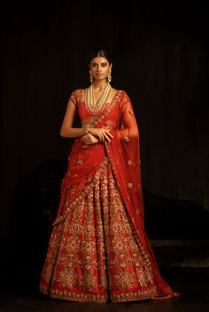 This ribbon red paneled raw silk lehenga is ornamented with intricate zardosi embroidery. The dusty pink resham threads stand out against the deep red and the subtle champagne crystals give the whole lehenga a subtle glamour. Teamed with a wide necked brocade cholee and a matching deep red dupatta, this lehenga is perfect for pheras. #bridal #trends #bridal2017 #bridalfashion #bridaldress #weddinglehenga