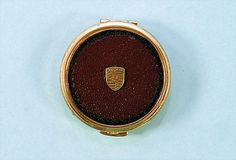 PORSCHE, D 60's/70's, small pill box, gold,  coated with leather, with put on Porsche logo, rare.