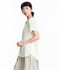 PREMIUM QUALITY. Short-sleeved silk blouse. Rounded hem with slits and overlapping panels at sides.