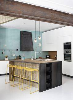 RØFT KJØKKEN: Kjøkkenøya, produsert av Bolt Metall, er selve navet i allrommet. Herfra har man full oversikt. Innredningen er dimensjonert for røff bruk. Benkeplaten er i bambus, og hjørner og hyller er i stål. Innredningen er designet av den italienske arkitekten Andrea Ravagnani i designstudioet NORDS. Barstolen er fra Hay. Veggen er kledd med fliser fra Vitra.