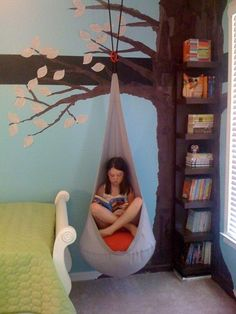 i love the way this cute reading chair is hanging in front of this awesome tree mural with shelves on it!