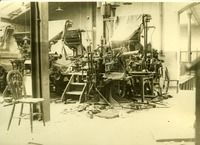 A printing press which has suffered extensive damage  -- Photograph of a printing press which has suffered extensive damage; bits of the press are scattered on the floor (possibly the offices of the Cork Examiner newspaper offices which were destroyed by the IRA on August 1922).
