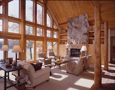The great room cathedral ceiling is lined with white cedar paneling and structural log purlins. The custom gable glass and heavy white cedar trim fill the entire wall.