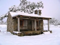 This stone house looks sturdy, but that tree looks to close for comfort...