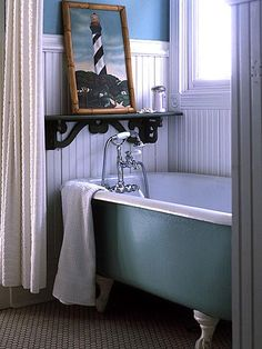 Salvaged Bath ~ Light aqua covers a salvaged clawfoot tub in a glossy oil-base enamel. The lighthouse painting is a treasure purchased at a junk shop for under 100 dalllors.
