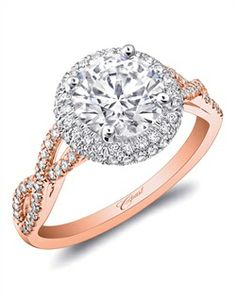 A round center stone in rose and white gold.  Halo encrusted in diamonds, framed by strings of diamonds which twist down the sides of the finger.  From Coast Diamond