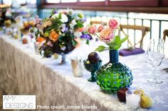 A variety of different colored and shaped vases with simple tulips and Roses and fruit placed down the head table. @janaeshields #reception Location Thomas Fogarty Winery