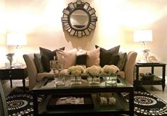 The loveseat with an abundance of pillows in various shades, mismatched (yet they compliment each other) side tables, fancy and fun area rug, and glass accented coffee table with hydrangeas in vases