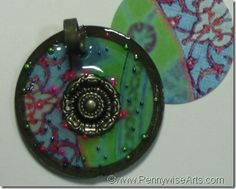 This is a large scrapbook brad made into a charm for a pendant.  By Suzanne Glazier www.PennywiseArts.com