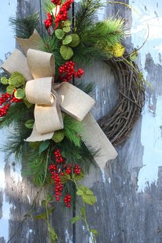 grapevine wreath with greenery, berries and a burlap bow