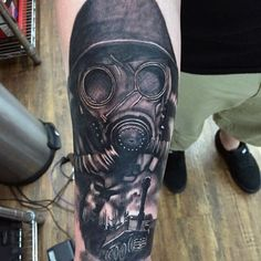 Realistic looking military soldier in gas mask with tank tattoo on arm
