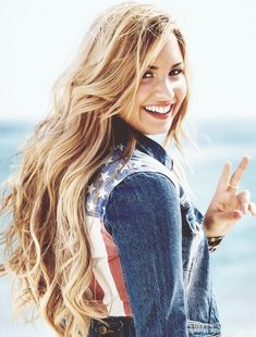 Demi Lovato Hairstyles: Blonde Curls with that cute use flag jacket looks really good