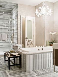 equator marmara marble tile in multiple shades of gray in the shower, on the tub surround, on the floor. black and white animal print stool = fluid counterpoint to geometric quality of marble. walls covered in silvery paper bring metallic sparkle