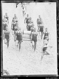 SURF LIFE SAVING REEL In 1906, Lyster Ormsby of the Bondi Surf Bathers Lifesaving Club designed the surf life saving reel to allow a lifesaver wearing a vest with a rope attached to reach a distressed swimmer. Photo shows a group of surf life savers marching with a life saving reel at Manly ca. 1920s