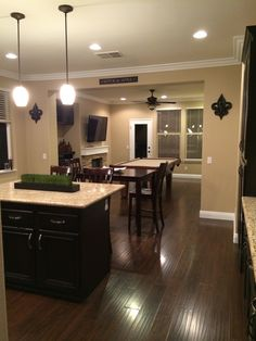 """Kitchen and pool room. Items remodeled: -From tile and carpet to laminate -White tile counter top to granite counter top -Oak cabinets to espresso stained cabinets -Fluorescent lights to can lights and drop accent lights -added 5"""" baseboard -added crown molding -paint Shermin Williams Nomadic Desert"""
